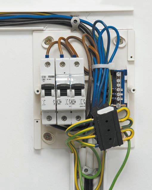 Небольшой щиток на 3 автомата со снятой панелью: провода заземления соединены вместе при помощи специальной клеммы, нолевые (синего цвета) — при помощи шины, расположенной справа от автоматов